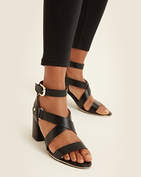 High block heel black sandals with strap over toes, straps crossing over foot and buckled strap at ankle