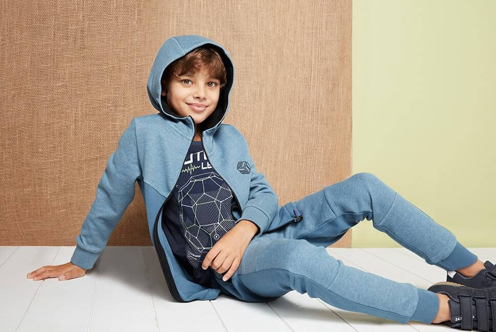 Two-tone steel blue hoodie with small cube logo graphic with words cool vibes, worn with matching blue jogging bottoms