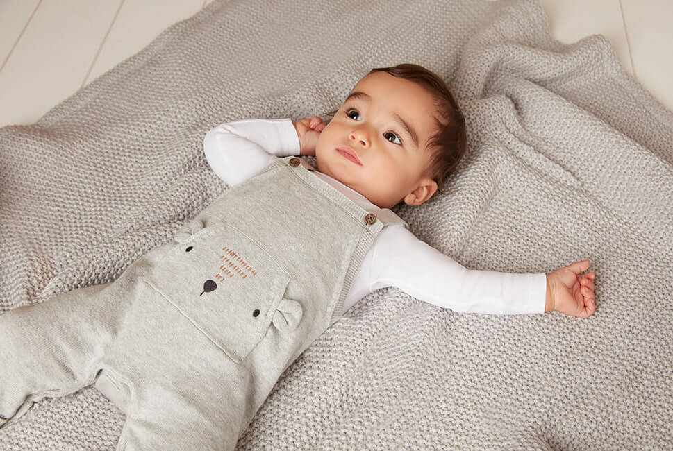 Pale grey knitted dungarees with cute bear face and ears on front kangaroo pocket. Comes with long sleeve white top