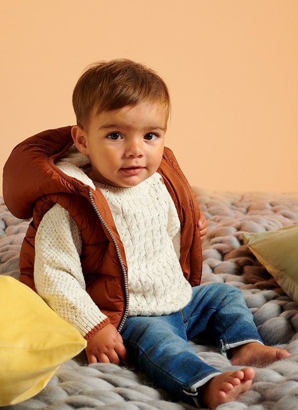 Rust brown padded gilet worn over cable knit oatmeal jumper with rust stripe at cuffs