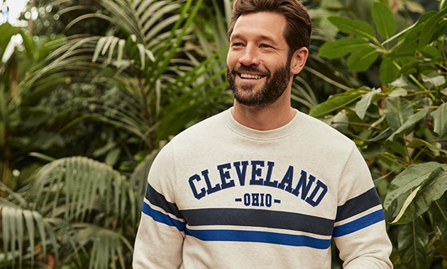 Cream jumper with 'Cleveland' in block black text with blue outline across the chest. Single thick black stripe and blue stripe across the chest and sleeve
