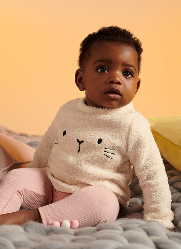 Long sleeve cream fleece top with bunny eyes, nose and whiskers in black stitching, paired with powder pink ribbed leggings