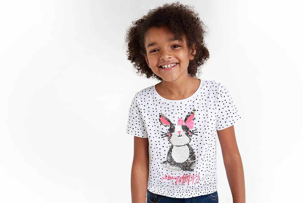 White T-shirt with black spots, and grey and white sequin bunny on front, with words always hoppy in pink