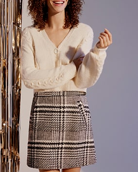 Cropped, buttoned cardigan with cable knit detail. Worn with black and white dogtooth tweed mini skirt