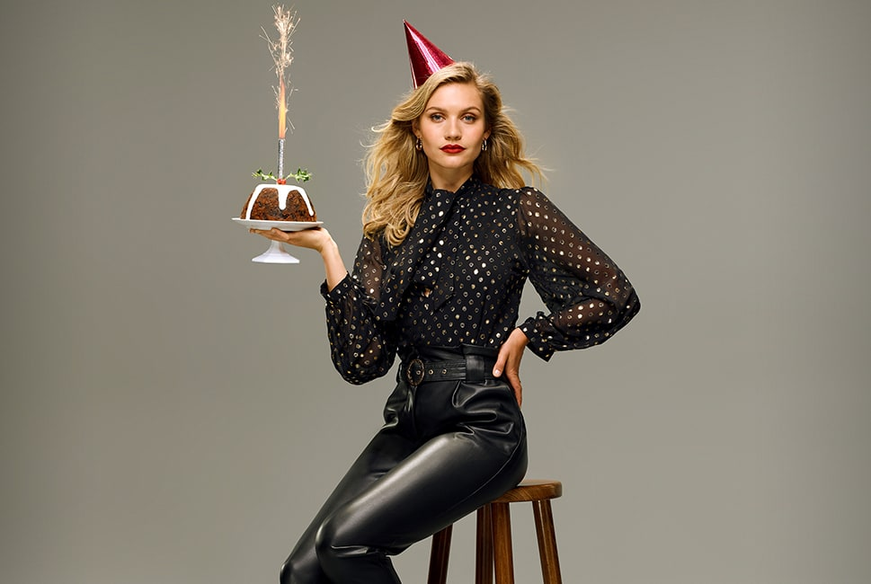 Sheer black blouse with large gold sequins, frilled hems on the sleeve and a pussybow neck, worn with black faux leather trousers