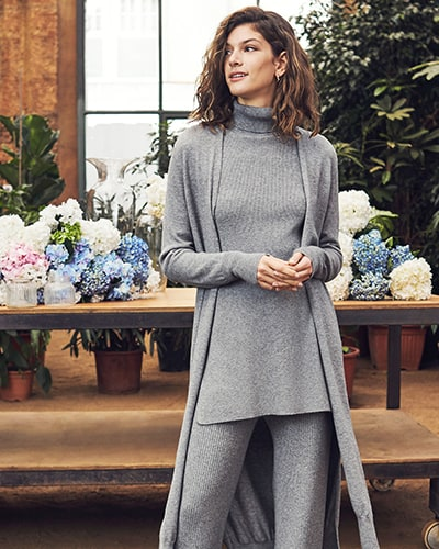 Ladies' light grey, ribbed, longline roll neck sweater. Worn with light grey, rib knit, wide leg trousers