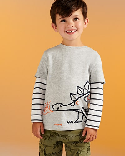 Black and white striped long sleeves under a grey T-shirt with black and orange dinosaur graphic