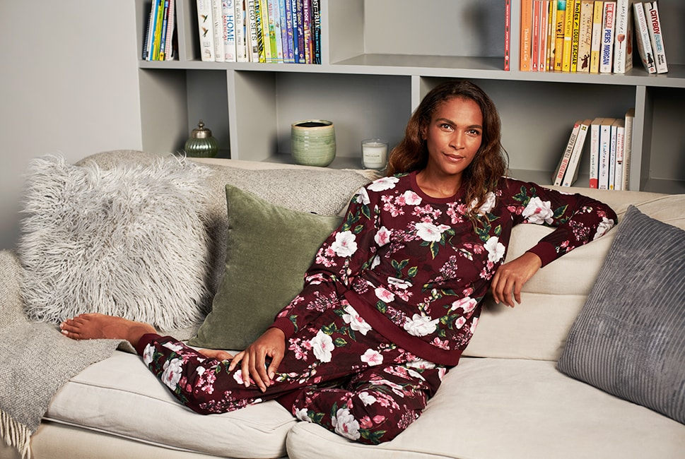 Plum long sleeve pyjama top with cuffed sleeves and a plum trim on the collar and bottom. There's an all-over print of white and pink flowers with green leaves. Comes with matching pyjama bottoms